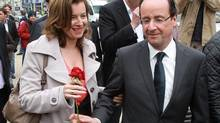 In this May 5, 2012 file photo, French Socialist Party candidate for the presidential election Francois Hollande, right, offers a rose to his companion Valerie Trierweiler, in Tulle, southwestern France. The woman considered France's first lady was hospitalized after a report the president is having an affair with an actress, her office said Sunday, as a poll was released showing the French shrugging off any liaison as none of their business. (Bob Edme/AP)