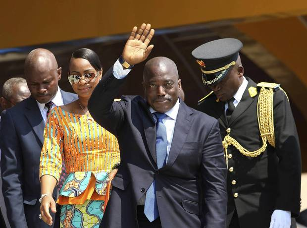 In this Thursday, June 30, 2016 photo, Congolese President Joseph Kabila, center, waves as he and others celebrate independence for the Democratic Republic of Congo in Kindu, Congo.