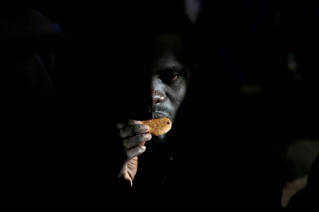 A migrant eats a biscuit on the Migrant Offshore Aid Station ship Topaz Responder after being rescued off the coast of Libya on June 23, 2016.