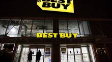 People peer into a Best Buy storefront on Dundas and Bay streets in Toronto on Dec. 25, 2011. (Michelle Siu For The Globe and Mail)