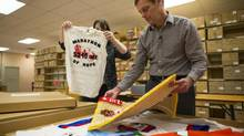 Darrell Fox and Marnie Burnham, manager of the regional archive program, look over the Fox family's memorabilia of Darrell's brother Terry Fox at the Archives Canada Storage facility in Burnaby, Dec. 5, 2013. (John Lehmann/The Globe and Mail)