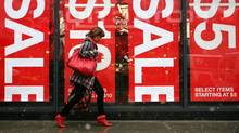 A shopper passes 'sale' signs as she walks past a store window in this file photo. (Mark Lennihan/AP)