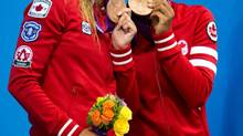 Canada's Emilie Heymans and Jennifer Abel celebrate their bronze medals following the women's synchronised 3-metre springboard final at the Aquatic Centre in the Olympic Village at the 2012 Summer Olympics in London on Sunday, July 29, 2012. (Sean Kilpatrick/THE CANADIAN PRESS)