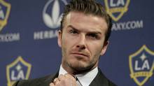 FILE - In this Jan. 19, 2012 file photo, Los Angeles Galaxy's David Beckham fixes his tie during a news conference in Los Angeles. (Associated Press)