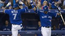 Toronto Blue Jays Jose Reyes (left) celebrates with Jose Bautista after hitting a homer off Minnesota Twins pitcher Scott Diamond during fifth inning AL baseball action in Toronto on Sunday July 7, 2013. (The Canadian Press)