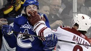 Defenseman Keith Ballard #2 of the Phoenix Coyotes (R) gets in the face of center Henrik Sedin #33 of
