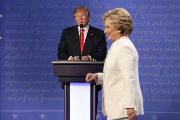 Donald Trump waits behind his podium as Hillary Clinton makes her way off the stage after the third presidential debate at UNLV in Las Vegas on Oct. 19, 2016.