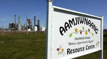 A sign for the Aamjiwnaang First Nation Resource Centre is located across the road from a chemical plant in Sarnia, Ont. (Craig Glover/The Canadian Press)