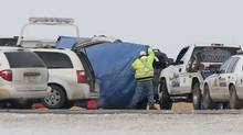 A tarp is placed over a Ford SUV on an Alberta highway after three of its occupants were shot and killed on Dec. 15. Shayna Conway, the driver, is in hospital recovering from her wounds. (Chris Bolin for The Globe and Mail)