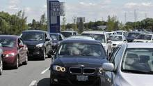 Hundreds of cars sit unmoving on the 401 exit ramp waiting to enter the parking lot at the Toronto Premium Outlets Grand Opening in Milton, August 1, 2013. (J.P. MOCZULSKI For The Globe and Mail)