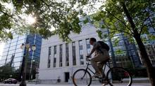 A cyclist passes the Bank of Canada in Ottawa in this file photo. The bank sets its interest rate on Wednesday (Adrian Wyld/THE CANADIAN PRESS)