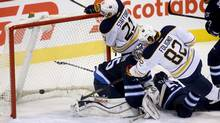 Buffalo Sabres' Marcus Foligno (82) appears to score a goal on Winnipeg Jets' goaltender Al Montoya (35) as Sabres' Drew Stafford (21) knocks the net off the mooring in the first period of Tuesday's game in Winnipeg. After a review, the goal was disallowed. (TREVOR HAGAN/THE CANADIAN PRESS)