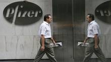 A pedestrian walks past the Pfizer world headquarters in New York. (Mary Altaffer/The Associated Press/Mary Altaffer/The Associated Press)