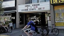 A cyclist rides past the Ridge Theater in Vancouver, BC, August 25, 2010 (Lyle Stafford for the Globe and Mail)