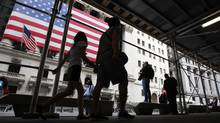 Commuters walk past the New York Stock Exchange. (BRENDAN MCDERMID/REUTERS)