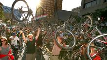 A groups of cyclists raise their bikes on Bloor Street in Toronto, in tribute to bike courier Darcy Allan Sheppard. (Fernando Morales/The Globe and Mail/Fernando Morales/The Globe and Mail)