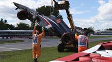 Track workers remove the car of Sauber driver Esteban Gutierrez of Mexico after a crash at the Canadian Grand Prix, Saturday, June 8, 2013 in Montreal. A race-track worker was killed Sunday after being crushed by a crane shortly after the Formula One race ended. (Tom Boland/THE CANADIAN PRESS)