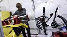 Evan Walsh helps set up the linear impactor to simulate a football collision. Research assistants in the neurotrauma impact science lab at the University of Ottawa are developing new 3-D impact protocol for evaluating helmet safety in Ottawa, Sept. 19, 2011. (Blair Gable for the Globe and Mail/Blair Gable for the Globe and Mail)