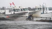 A lobster fisherman slips but holds on while trying to secure lines to his fishing boat after the floating dock broke apart during Tropical storm Arthur in Escuminac, N.B. on Saturday, July 5, 2014. (Diane Doiron/THE CANADIAN PRESS)