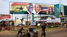 Labourers in Ghana's capital, Accra, push a cart past a billboard depicting Ghana's President John Atta Mills and United States President Barack Obama. Mr. Obama visited Ghana in July, 2009 (FINBARR O'REILLY/FINBARR O'REILLY/REUTERS)