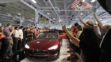 In June, 2012, Tesla workers cheer the first Tesla Model S cars sold during a rally at the Tesla factory in Fremont, Calif. (PAUL SAKUMA/AP)