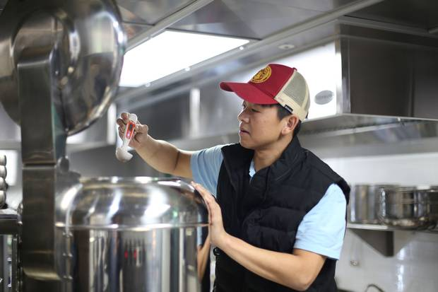 Mr. Yim checks the temperature of his Pyongyang naengmyeon, which is chilled to just above freezing.