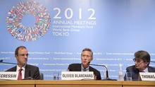 The International Monetary Fund's economic director of research Olivier Blanchard, deputy director Jorg Decressin (L) and division chief Thomas Heibling (R) hold a news briefing on the World Economic Outlook at the Tokyo International Forum in Tokyo. (REUTERS)
