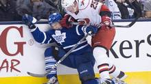 Toronto Maple Leafs forward Matt Frattin gets taken out by Carolina Hurricanes defenceman Joni Pitkanen during a March 28 game (Nathan Denette/THE CANADIAN PRESS)