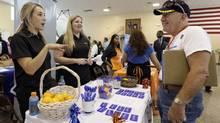 In this photo taken Wednesday, July 16, 2014, job seeker U.S. Army veteran John Godman, right, talks to recruiters Nicole Rushton, left, and Megan Hogan, centre, at a Hiring Fair For Veterans in Fort Lauderdale, Fla. (Alan Diaz/AP)