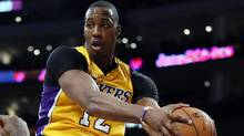Los Angeles Lakers' Dwight Howard pulls in a defensive rebound against the Phoenix Suns during the first half of an NBA basketball game on Tuesday, Feb. 12, 2013, in Los Angeles. (Associated Press)