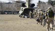 The last Canadians involved in the NATO training mission in Afghanistan board a U.S. Chinook helicopter as they leave the International Security Assistance Force headquarters in Kabul, Afghanistan March 12, 2014. (HANDOUT/Reuters)