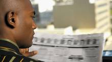Man reading a newspaper. (Stockbyte/Getty Images)