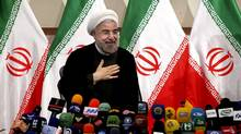 Iranian newly elected President Hasan Rowhani, places his hand on his heart as a sign of respect after speaking at a press conference in Tehran, June 17, 2013. (Ebrahim Noroozi/AP)