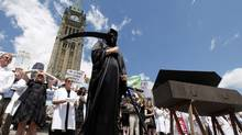 A protestor wearing a Grim Reaper costume stands on Parliament Hill during a rally on July 10, 2012 in Ottawa to protest the federal government's cuts to science policies. (Fred Chartrand/The Canadian Press)