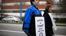 Louella Vincent, left, and Sue Munn of the Hospital Employees' Union walk in solidarity with other community living workers from various unions outside the Richmond Caring Place in Richmond, B.C. (Rafal Gerszak For The Globe and Mail)