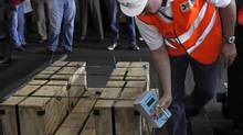 A Dominican customs worker takes measurements of a shipment of gold belonging to Barrick Gold that was detained for four days. (REUTERS)