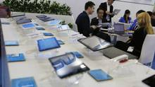 In this April 12, 2014 photo, a potential buyer, left, studies the Chinese made tablets in a booth at the Global Sources Spring China Sourcing Fair in Hong Kong. (Kin Cheung/THE ASSOCIATED PRESS)