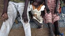 A South Sudanese girl sits between her parents, who have leprosy, in Mogiri in 2007. A new report from the World Health Organization shows that 232,857 cases of leprosy were reported worldwide in 2012. – a far cry from the five million cases a year recorded until the early 1980s, but still far too many to even dream of eradicating the disease. (EDWARD OU/REUTERS)