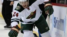 Minnesota Wild left wing Matt Cooke reaches to control the puck against the Colorado Avalanche in the first period of Game 2 of an NHL hockey first-round playoff series on Saturday, April 19, 2014, in Denver. (Jack Dempsey/THE ASSOCIATED PRESS)