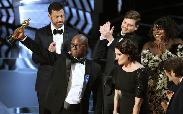 Barry Jenkins, writer and director of Moonlight, holds up the Best Picture Oscar in front of host Jimmy Kimmel (rear) as he stands with Producer Adele Romanski.