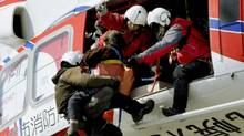 An elderly person is rescued by helicopter from the roof of an elementary school after an earthquake and tsunami in Sendai, northeastern Japan March 12, 2011 (KYODO/Reuters/Kyodo)