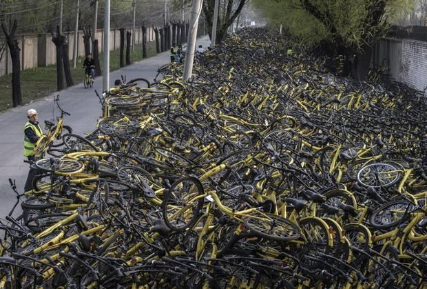 A worker from bike share company Ofo puts a damaged bike on a pile at a makeshift repair depot for the company where thousands of derelict bikes are being kept after coming off the road.