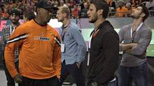 BC Lions' Geroy Simon (L) talks with Vancouver Canucks' Kevin Bieksa (2nd R) during the Lions' CFL game against the Calgary Stampeders in Vancouver, British Columbia October 6, 2012. Several players from the Canucks, who are currently locked out by the league during their labour dispute, attended the game. (ANDY CLARK/REUTERS)