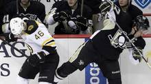 Pittsburgh Penguins' Sidney Crosby, right, collides with Boston Bruins' David Krejci along the boards in the first period of an NHL hockey game, Monday, Dec. 5, 2011, in Pittsburgh. (Gene J. Puskar/Associated Press)