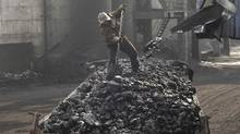 A labourer loads coal onto a truck at a coal mine in Changzhi, Shanxi province. (Reuters)