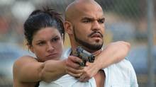 In a twist on the conventional action-thriller, Gina Carano (with Amaury Nolasco) plays the traditionally male part of rescuer.