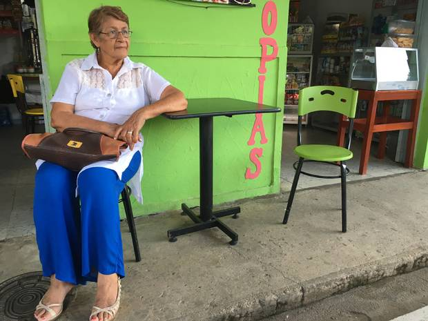 Maria Luisa Celis sits outside the building that the FARC attacked during a town council meeting she was attending in 2005. The building is now an ice cream and photocopy shop.