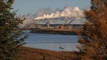 The Syncrude oil sands facility stands by a reclaimed lake near Fort McMurray, Alta. Ottawa has twice delayed the release of its plan to reduce greenhouse-gas emissions. (MARK RALSTON)