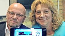 Scott Burton, president of Dolphin Digital Technologies, and wife Jamie Burton, director, display their viirtual company's web site on a computer. (The Canadian Press)
