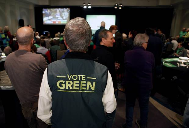 Green party supporters watch as results come in from election night.